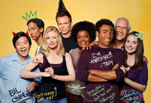 The cast of community all stand in single fine line while their yearbook signatures hover around them