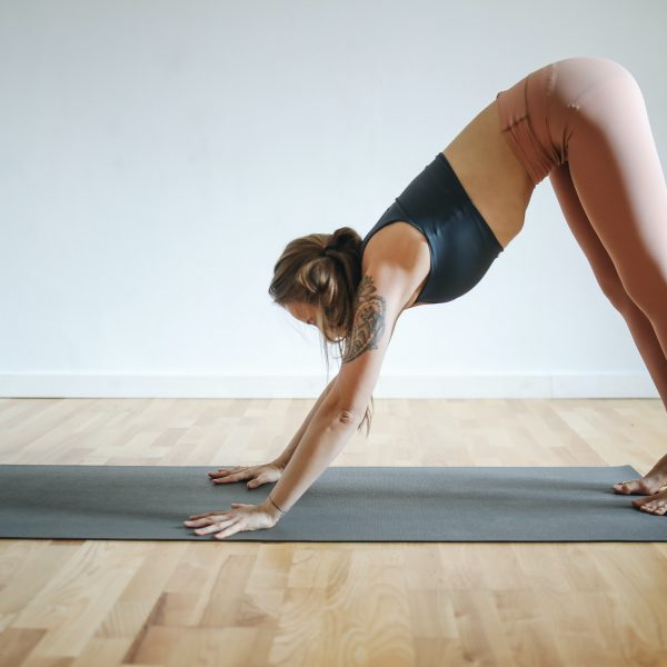 woman in black sports bra and brown leggings doing yoga