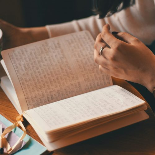 photo of person holding cup while journaling