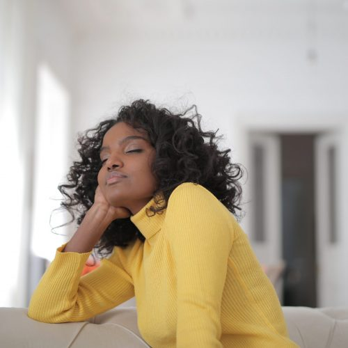 woman in yellow sweater taking a moment to relax and say thank you